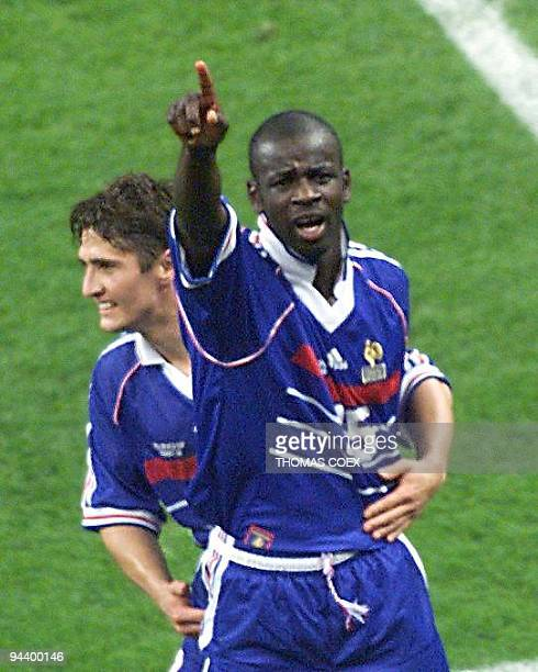 French Lilian Thuram celebrates with Bixente Lizarazu after France defeated Croatia 21 in their World Cup semifinal 08 July at the Stade de France in...