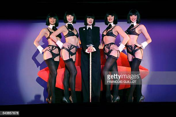 TOPSHOT French lingerie designer Chantal Thomass new guest artistic director of the Crazy Horse Paris show poses with dancers after a press...