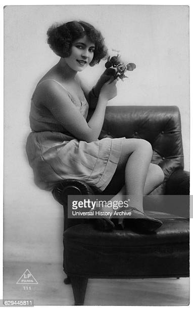 French Lingerie Model Seated on Arm of Chair Holding Flowers circa 1920