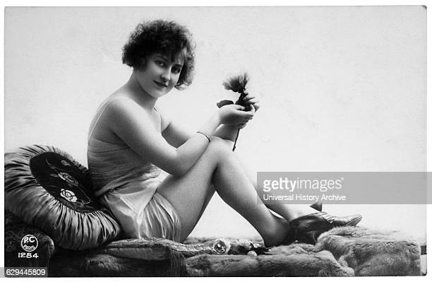 French Lingerie Model Seated on Chaise Lounge Holding Flower circa 1920