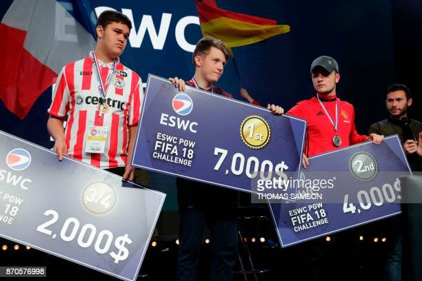French Lucas 'DaXe' Cuillerier from PSG Esports Team winner of the ESWC Fifa 18 Challenge poses with his trophy and ceremonial check on November 5...
