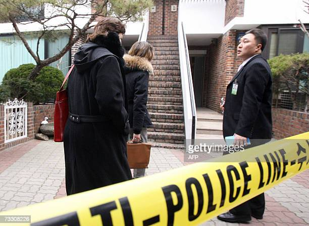 French magistrate MarieDominique BoulardPaolini and other investigators walk past a yellow police line to visit the Seoul house where two infants...