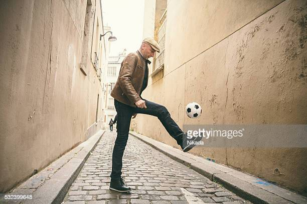 french man playing with soccer ball at urban street