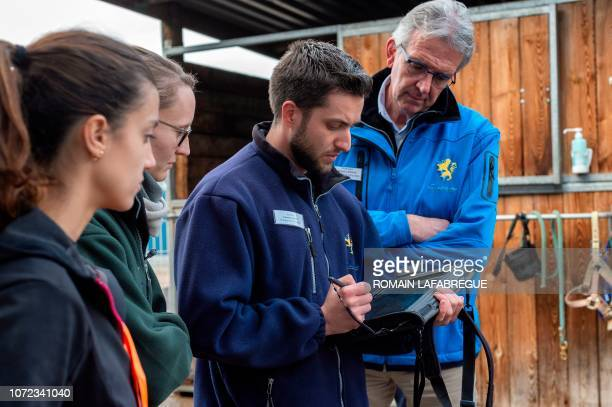 French manager of Equine Health Centre and surgeon Olivier Lepage looks at a tablet computer with his staff members as they analyse the limbs of a...