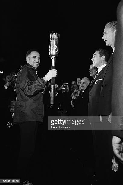French marathon champion Alain Mimoun holding Olympic Flame during the opening ceremony of the 1968 Winter Olympics in Grenoble