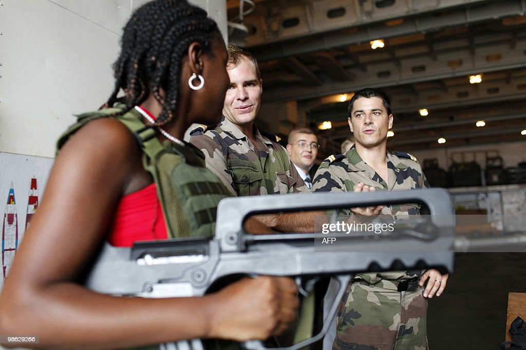 A French Marine soldier gives explanations about a FAMAS assault rifles, on March 17, 2010 in Fort-de-France on the French island of La Martinique, in the eastern Caribbean Sea during the National Defense Information Day (JAPD) of a group of 34 people, on board of the French helicopter-carrier Jeanne d'Arc. The Jeanne d'Arc is a Naval Academy 182-metre-long ship carrying a crew of 585 officers and sailors, doing its last trip as training vessel.