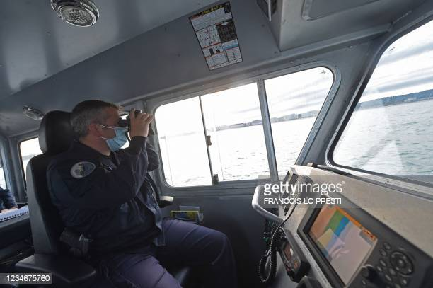 French Maritime Gendarme from Boulogne-Sur-Mer, south of the port of Calais, looks through a pair of binoculars as he and his colleagues search for...