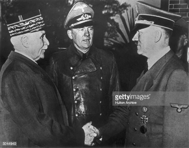 French Marshal and Vichy leader HenriPhilippe Petain and Nazi leader Adolf Hitler share the famous 'handshake at Montoire' while interpreter Colonel...