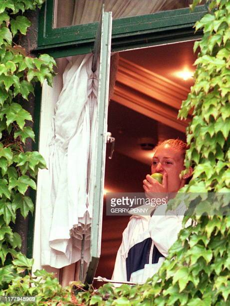French Mary Pierce munches an apple as she looks out of a window 29 June in the ivy covered walls of the All England Lawn Tennis and Croquet Club at...