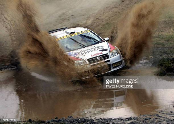 French Mathieu Biasion and codriver Eric Domenech speed their Fiat Punto Super 1600 through a muddy pool during the Acropolis Rally of Greece in...