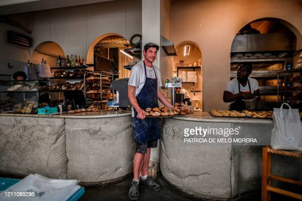 French Matthieu Raud baker, poses for a photo holding a tray with bread at ISCO artisanal bakery in Lisbon on April 23, 2020 during the COVID-19...