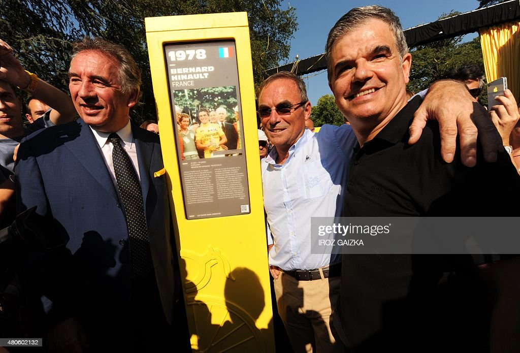 French Mayor of Pau Francois Bayrou, 5-time Tour de France winner French Bernard Hinault and French writer Christian Laborde pose next the totem of Bernard Hinault as part of the 'Tour of Giants,' a memorial of 101 totems dedicated to the 101 winners of the Tour de France in Pau on July 13, 2015.