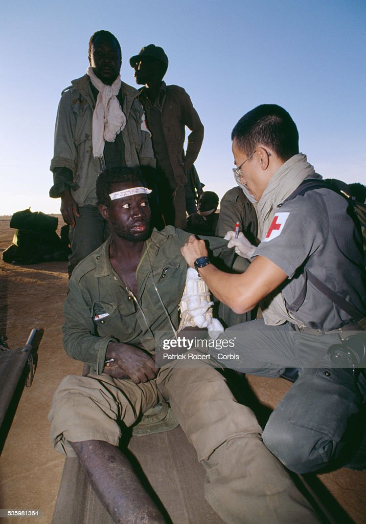 A French medic with the Red Cross administers First Aid to a rebel soldier with the Forces Armées Nationales Chadiennes (FANT), or National Army of Chad, before evacuating the troops onto a Transall C-160 aircraft. Lead by Deby, the Chadian Chief of Staff, the FANT rebellion seized power from head of state Hissen Habre in a French- and Libyan-backed military coup. Deby later won the first multi-party Chadian presidential vote in 1996.