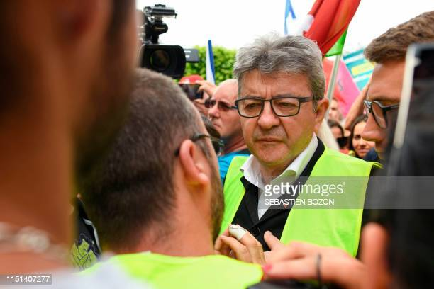 French member of Parliament and leader of the leftist La France Insoumise party Jean-Luc Melenchon speaks with a protestors wearing a Yellow Vest...