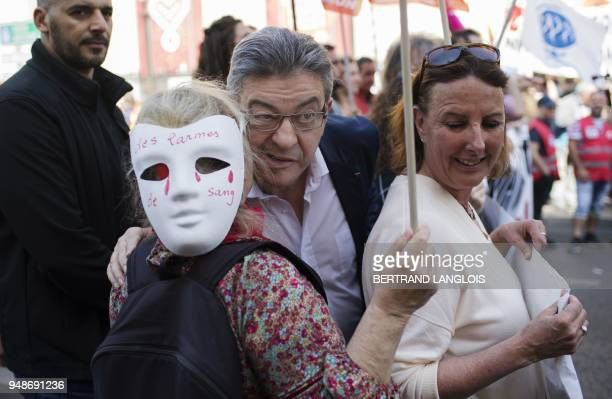 TOPSHOT French member of Parliament and leader of the leftist La France Insoumise party JeanLuc Melenchon greets a protester as he takes part in a...