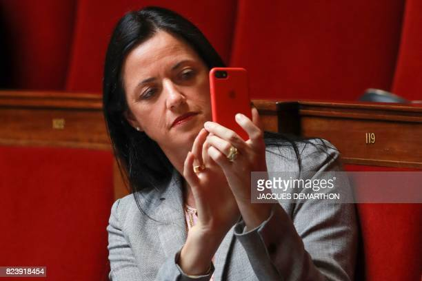 French Member of Parliament for Les Republicains opposition party, Valerie Bazin-Malgras uses her mobile phone as she attends a debate on a draft law...