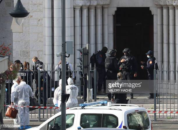 French members of the elite tactical police unit RAID enter to search the Basilica of Notre-Dame de Nice as forensics officers wait outside after a...