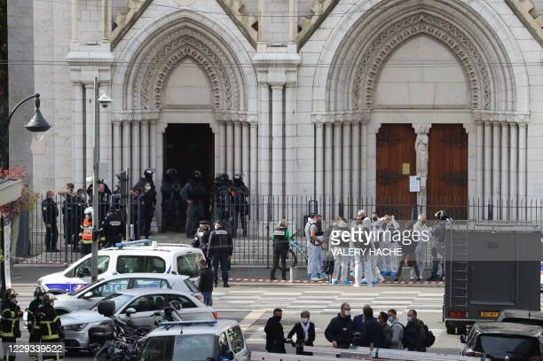 French members of the elite tactical police unit RAID enter to search the Basilica of Notre-Dame de Nice as forensics officers wait after a knife...