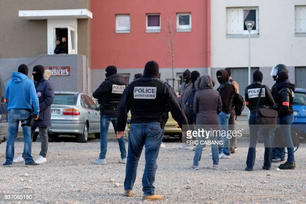 French members of the Police Judiciaire secure the area during a search operation at the Ozanam housing estate in Carcassonne southwestern France on...