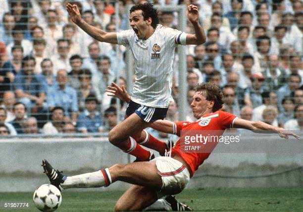 French midfiedler Michel Platini loses control of the ball as he is tackled by English defender Terry Butcher during the World Cup first round soccer...