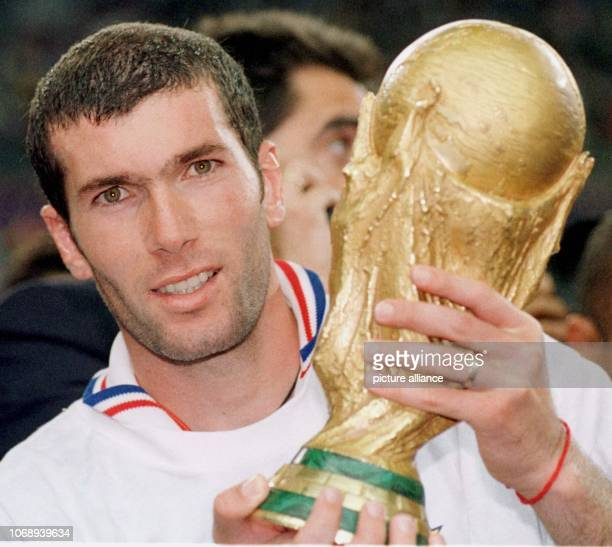 French midfielder and goalgetter Zinedine Zidane holds the World Cup trophy in his hands and smiles after the 1998 World Cup soccer game France...