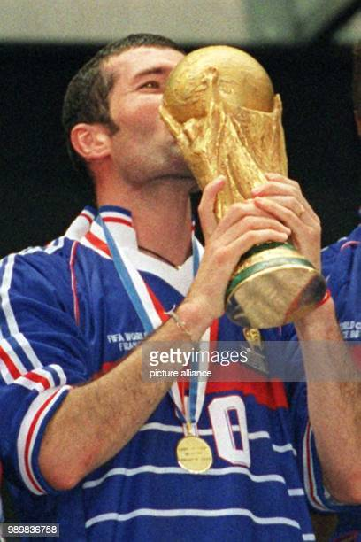 French midfielder and two time scorer in the final Zinedine Zidane kisses the World Cup after France wins the 1998 World Cup final against defending...
