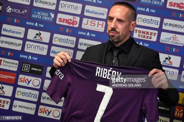French midfielder Franck Ribery holds his new jersey during a press conference held for his presentation as a new player of Fiorentina at the...