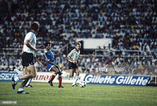 French midfielder Jean Tigana vies with West German players during the 1982 World Cup semifinal football match between West Germany and France on...