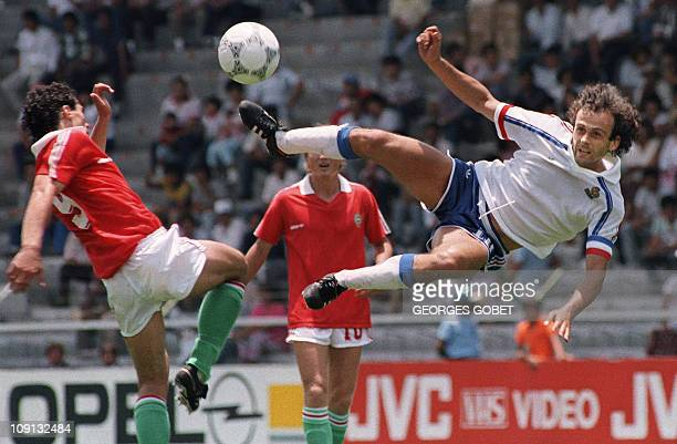 French midfielder Michel Platini attempts a volley as he is challenged by Hungarian Lazslo Dajka during the World Cup first round soccer match...
