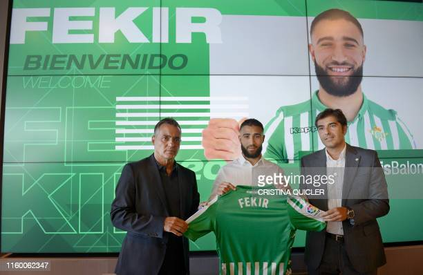 French midfielder, Nabil Fekir , poses with the president of Real Betis, Angel Haro and the team's director of football, Alexis Trujillo, during...