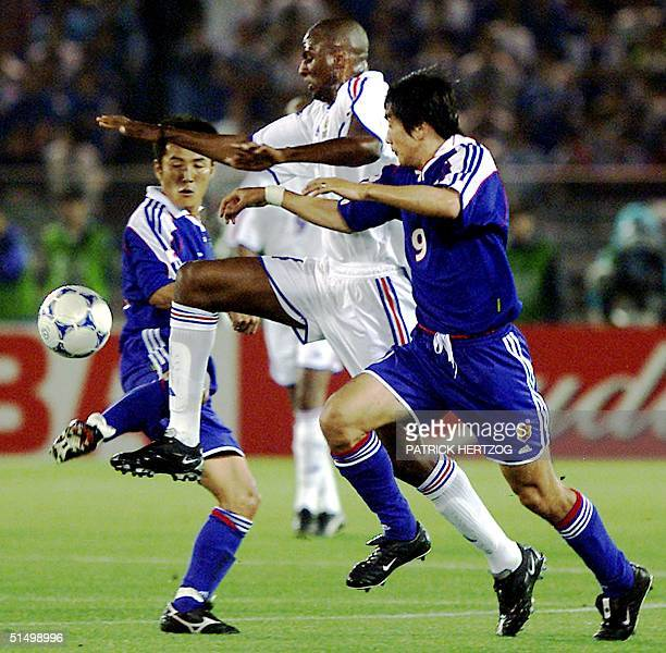 French midfielder Patrick Vieira fights for the ball with Japanese striker Akinori Nishizawa during their Confederations Cup final match at the...