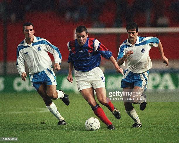 French midfielder Paul Le Guen controls the ball as two Israeli player surround him 13 October 1993 in Paris during a match counting for the...