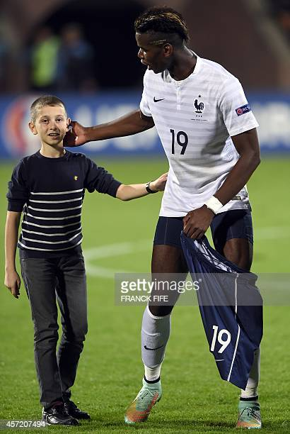 French midfielder Paul Pogba gives his shorts to a fan at the end of the friendly football match between Armenia and France on October 14 2014 at the...