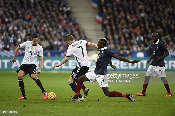 French midfielder Paul Pogba tackles Germany's midfielder Bastian Schweinsteiger during a friendly international football match between France and...