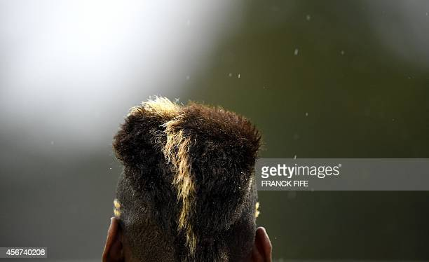 French midfielder Paul Pogba's haircut is seen as he arrives for a training session in Clairefontaine-en-Yvelines on October 6, 2014 ahead of a...
