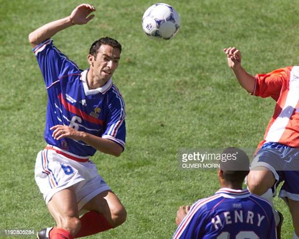French midfielder Youri Djorkaeff tries to control the ball as team-mate Thierry Henry is looking on 28 June at the Felix Bollaert stadium in Lens,...