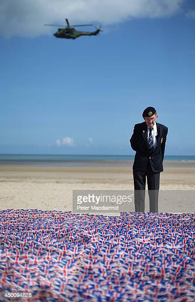 French military helicopter passes overhead as WW2 veteran Fred Holborn from the Fleet Air Arm looks at British Legion Union flags carrying thank you...