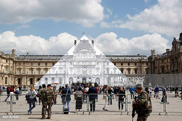 French military patrol in front of the artwork of French street artist and photographer JR displayed on the Louvre Pyramid on May 25 2016 in Paris...