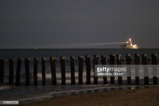French military ship shines light to search for migrant boats attempting to reach Britain in the English Channel off the northern French coast...