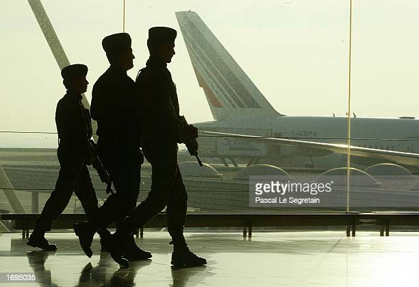 French military soldiers and a policeman walk inside Terminal Two of Charles De Gaulle airport December 19 2002 in Roissy France The French...