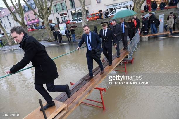 French Minister attached to the Minister of Ecological and Inclusive Transition Sebastien Lecornu walks on planks above the flooded banks of the...