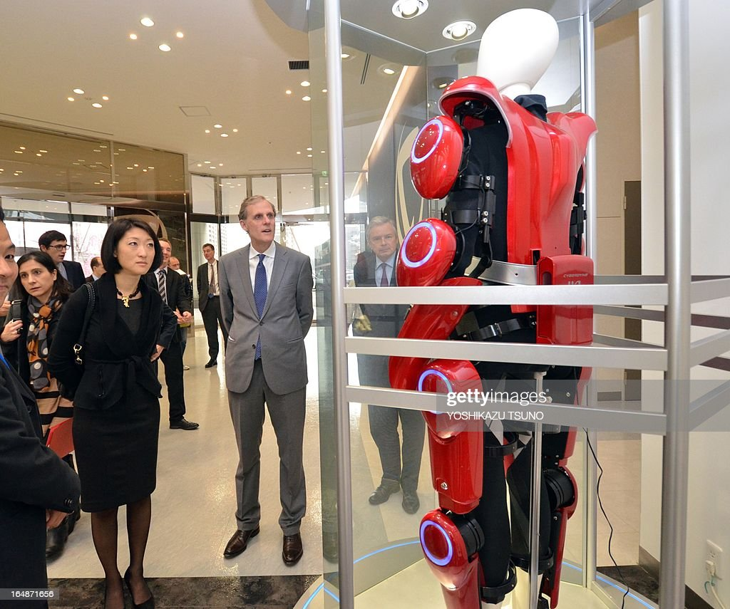 French Minister Fleur Pellerin (L) looks at a prototype model of a robot suit Hybrid Assistive Limb (HAL), developed by University of Tsukuba professor Yoshiyuki Sankai at his company Cyberdyne in Tsukuba, suburban Tokyo on March 29, 2013. The HAL, which is designed to learn the user's motion and assist the wearer's movement, can be used for the rehabilitation of disabled and assist elderly people. AFP PHOTO / Yoshikazu TSUNO