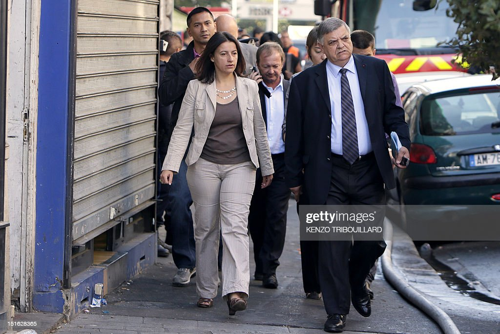 French Minister for Equality of Territories and Housing, Cecile Duflot (CL) and Seine-Saint-Denis' prefect Christian Lambert (CR) arrive on the scene of a fire on September 9, 2012 in Saint-Denis, near Paris. Two people died, four were seriously injured and eleven have been slightly injured in the fire, of undetermined origin, that broke out in an habitation building in the center of Saint-Denis during the night from Saturday to Sunday.