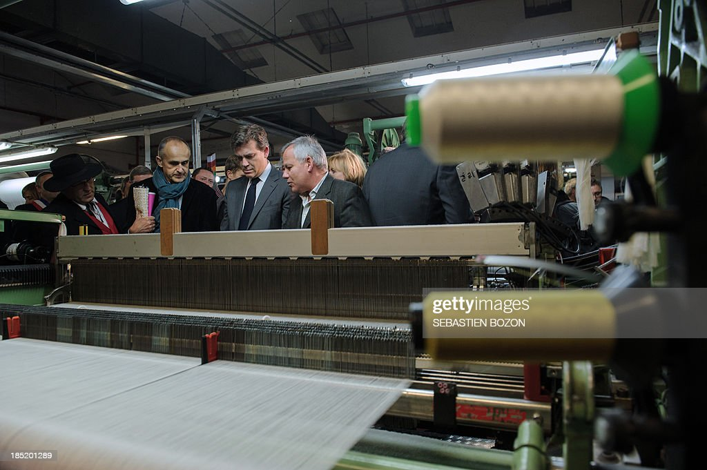 French minister for Industrial Recovery and Food Industry Arnaud Montebourg (C) speaks with Christian Didier (R) and Pierrez Schmitt (L), the potential buyers of the Virtuose textile factory which is already into liquidation, during a visit in Hirsingue, eastern France, on October 18, 2013.