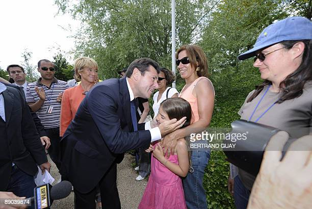 French minister for Industry Christian Estrosi salutes on strike workers and their relatives as he arrives for a visit to the Nortel plant factory in...
