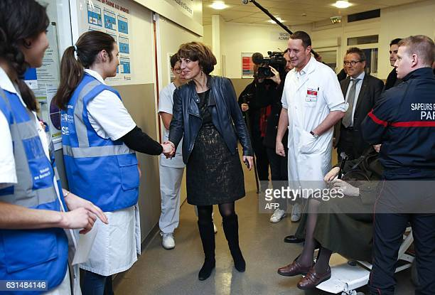 French Minister for Social Affairs and Health Marisol Touraine flanked by the chief of emergency service Sebastien Beaune shakes hands with emergency...