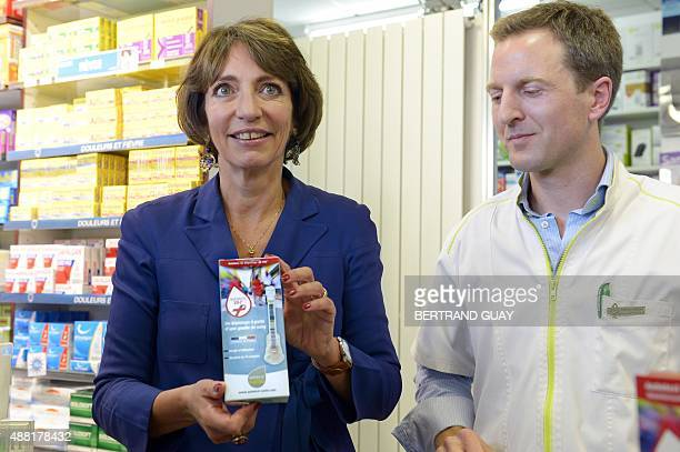 French Minister for Social Affairs Health and Women's Rights Marisol Touraine poses for a photograph with a HIV self testing kit at a pharmacy in...