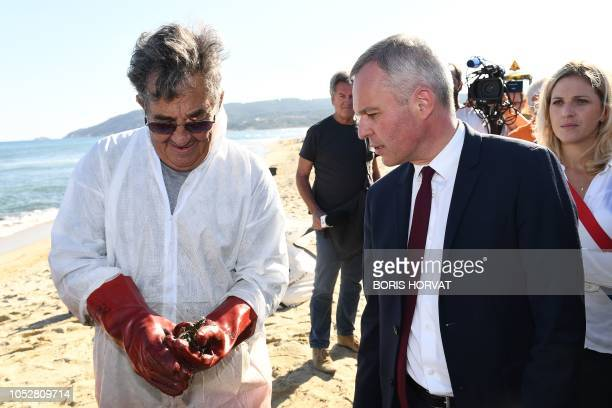 French Minister for the Ecological and Inclusive Transition Francois de Rugy talks with a worker cleaning hydrocarbon slabs from oil spill from two...