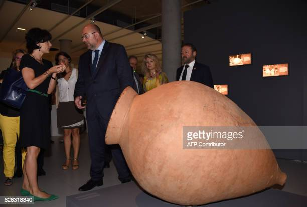 French Minister of Agriculture Stéphane Travert speaks with Georgia's Ambassador to France Sinadze Delaunay as they stand beside a terracotta wine...