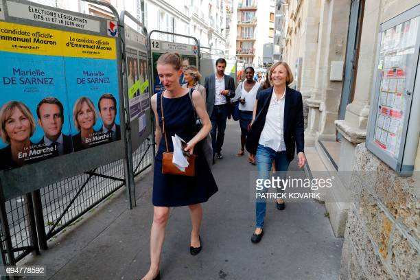 French Minister of European Affairs Marielle de Sarnez walks past election campaign posters picturing herself and French President Emmanuel Macron...